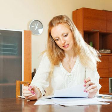Serious-blonde-woman-looking-at-financial-documents_web