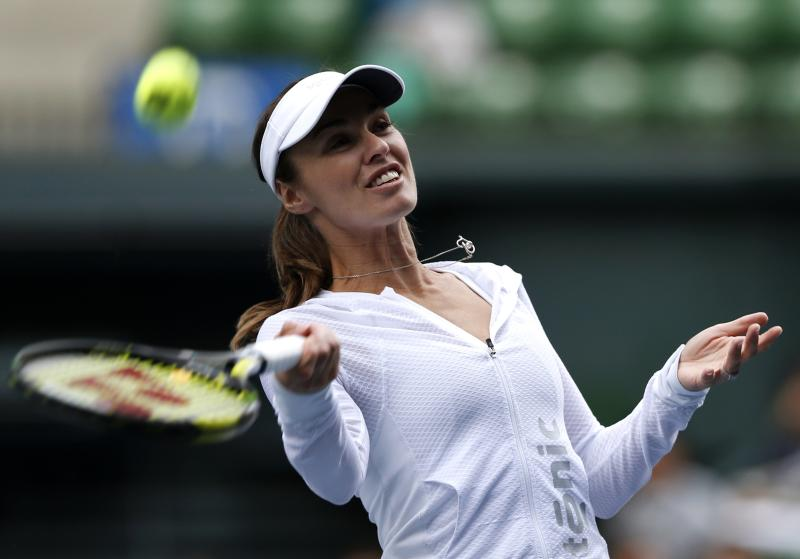 Hingis of Switzerland shoots autographed balls to fans after she played an exhibition tennis match with Sato, an 11-year-old Japanese tennis player, at the Pan Pacific Open tennis tournament in Tokyo