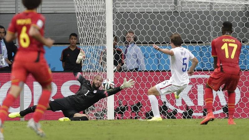 United States' goalkeeper Tim Howard (1) dives to make a save as Matt Besler (5) watches with Belgium's Divock Origi (17) during the World Cup round of 16 soccer match between Belgium and the USA at the Arena Fonte Nova in Salvador, Brazil, Tuesday, July 1, 2014. At left is Belgium's Axel Witsel