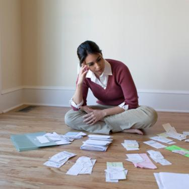 Woman-looking-at-bills-and-receipts-on-the-floor_web