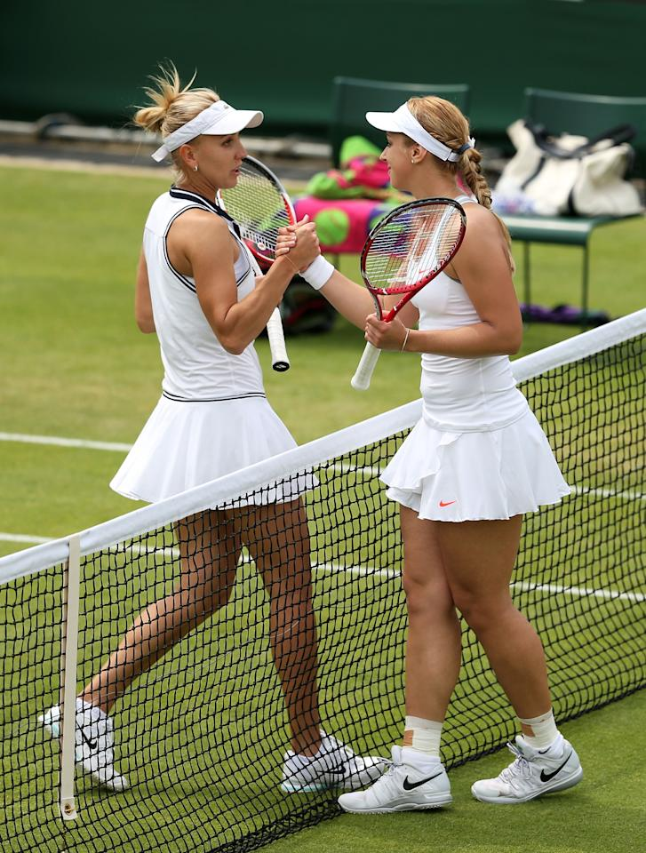 LONDON, ENGLAND - JUNE 27: Sabine Lisicki of Germany shakes hands at the net with Elena Vesnina of Russia after their Ladies' Singles second round match on day four of the Wimbledon Lawn Tennis Championships at the All England Lawn Tennis and Croquet Club on June 27, 2013 in London, England. (Photo by Clive Brunskill/Getty Images)