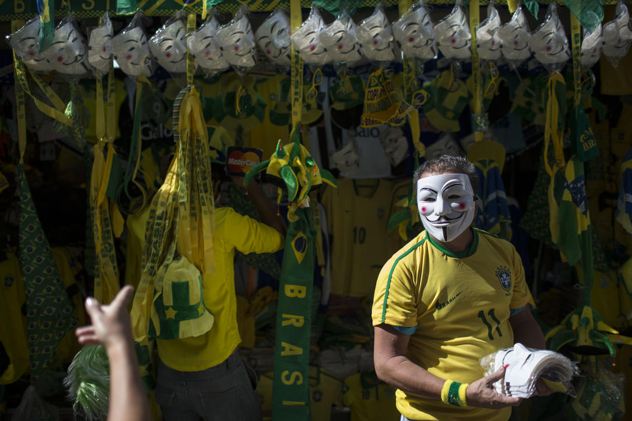 A vendor sells Guy Fawkes masks and Brazilian flags on the sidelines of a protest march moving toward the Mineirao stadium before a Confederations Cup semifinal soccer match between Brazil and Uruguay in Belo Horizonte, Brazil, Wednesday, June 26, 2013. The wave of protests that hit Brazil on June 17 began as opposition to transportation fare hikes, then expanded to a list of causes including anger at high taxes, poor services and high World Cup spending, before coalescing around the issue of rampant government corruption. (AP Photo/Felipe Dana)