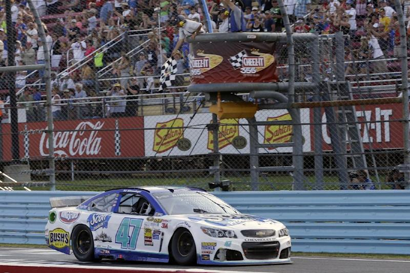 AJ Allmendinger (47) takes the checkered flag to win a NASCAR Sprint Cup Series auto race at Watkins Glen International, Sunday, Aug. 10, 2014, in Watkins Glen N.Y