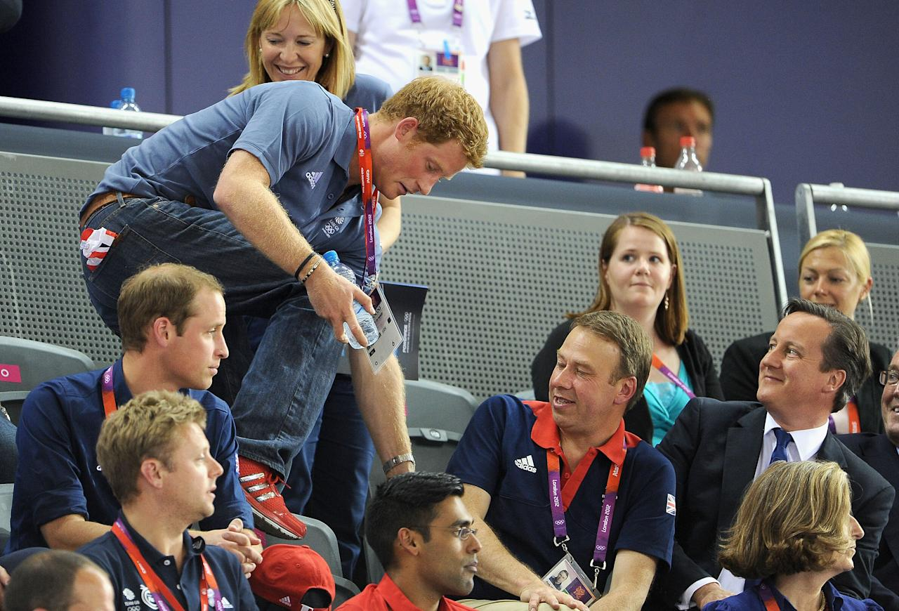 Prince Harry climbs over to his seat as Prince William; Duke of Cambridge (L) and Prime Minister David Cameron (R) look on his during Day 6 of the London 2012 Olympic Games at Velodrome on August 2, 2012 in London, England.  (Photo by Pascal Le Segretain/Getty Images)