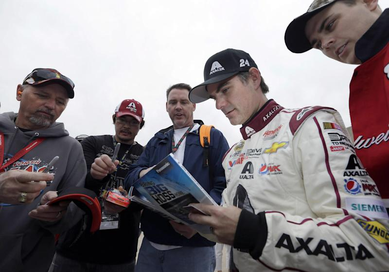 Jeff Gordon stops the sign autographs for fans after a practice session for the NASCAR Sprint Cup Series auto race at Texas Motor Speedway in Fort Worth, Texas, Saturday, April 5, 2014