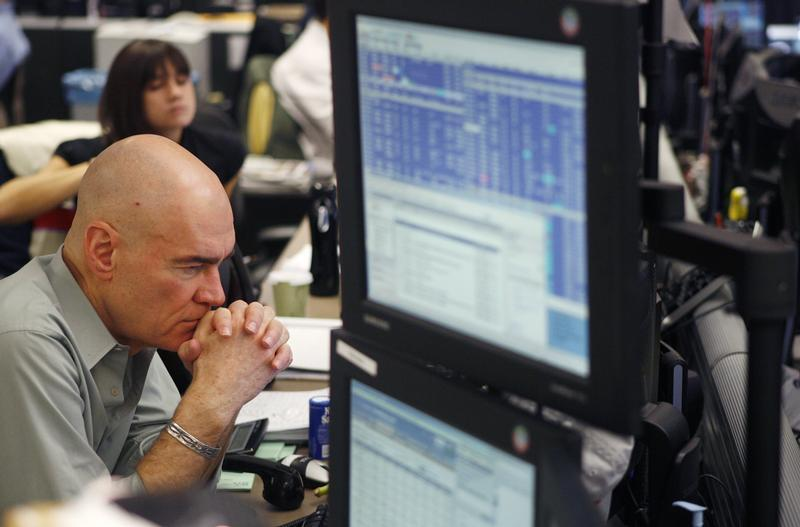 A broker waits for a phone call as he trades on the dealing floor at ICAP in Jersey City, New Jersey