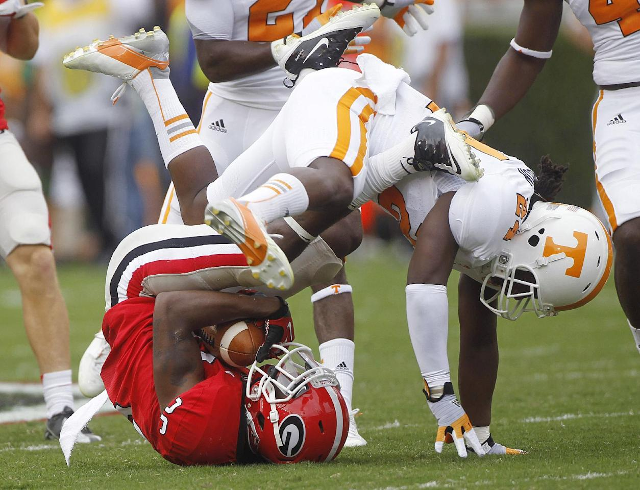 Georgia's Malcolm Mitchell (26) is tackled by Tennessee's Eric Gordon (24) as he fields a punt in the first half of an NCAA college football game in Athens, Ga., on Saturday, Sept. 29, 2012. (AP Photo/John Bazemore)