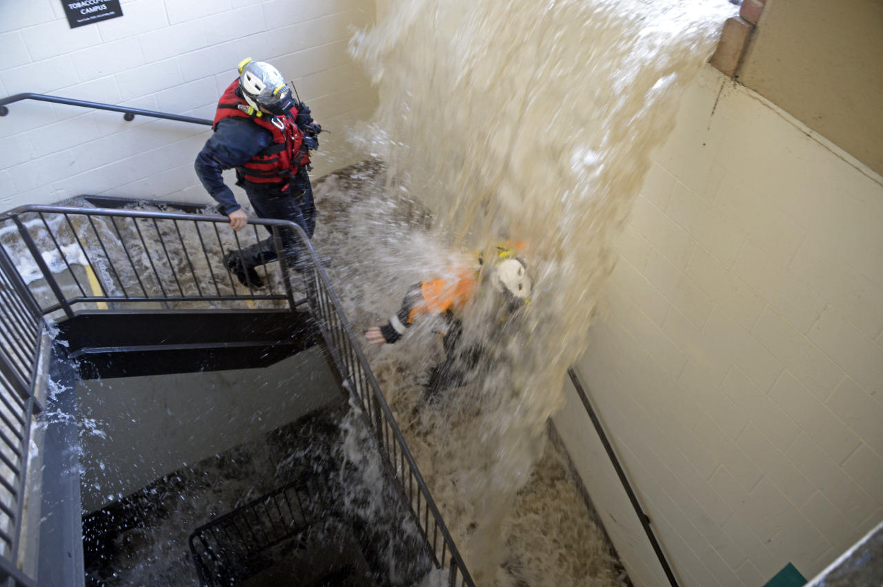 Workers walk down stairs to a parking structure as water cascades down on them on the UCLA campus after flooding from a broken 30-inch water main under nearby Sunset Boulevard inundated a large area of the campus in the Westwood section of Los Angeles, Tuesday, July 29, 2014. The 30-inch (75-centimeter) 93-year-old pipe that broke made a raging river of the street and sent millions of gallons (liters) of water across the school's athletic facilities, including the famed floor of Pauley Pavilion, the neighboring Wooden Center and the Los Angeles Tennis Center, and a pair of parking structures that took the brunt of the damage. (AP Photo/Mike Meadows)