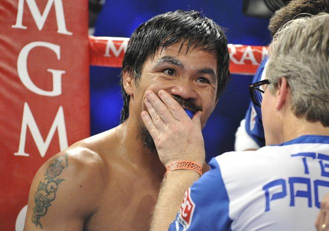 Trainer Freddie Roach (R) confers between rounds with Manny Pacquiao (L) of the Philippines during their WBO welterweight title match against Timothy Bradley of the US at the MGM Grand Arena on June 9, 2012 in Las Vegas, Nevada.  In what is being viewed as a highly controversial and unpopular outcome, unbeaten Bradley ended Pacquiao's long unbeaten run with a split decision victory over the Filipino ring icon.     AFP PHOTO / JOE KLAMARJOE KLAMAR/AFP/GettyImages