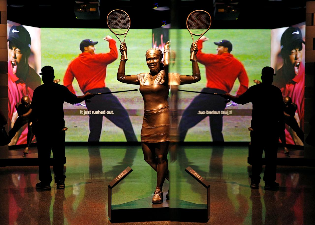Reflected in a mirror, a man points his cane toward images of golfer Tiger Woods and a statue of tennis great Serena Williams  during a media preview at the National Museum of African American History and Culture on the National Mall in Washington September 14, 2016. The museum will open to the public on September 24. REUTERS/Kevin Lamarque  FOR EDITORIAL USE ONLY. NO RESALES. NO ARCHIVES.