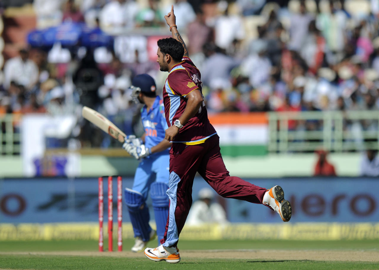 Ravi Rampaul of West Indies celebrates the wicket of Rohit Sharma of India during the second Star Sports One Day International (ODI) match between India and The West Indies held at the Dr. Y.S. Rajasekhara Reddy ACA-VDCA Cricket Stadium, Vishakhapatnam, India on the 24th November 2013  Photo by: Pal Pillai - BCCI - SPORTZPICS   Use of this image is subject to the terms and conditions as outlined by the BCCI. These terms can be found by following this link:  http://sportzpics.photoshelter.com/gallery/BCCI-Image-Terms/G0000ahUVIIEBQ84/C0000whs75.ajndY