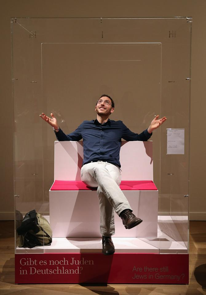 """BERLIN, GERMANY - APRIL 04:  Bill Glucroft, an American Jew living in Berlin, relaxes in between chats with visitors while sitting in his box in the """"live exhibit"""" portion of the exhibition """"The Whole Truth - Everything You Always Wanted To Know About Jews . . . """" at the Juedisches Museum (Jewish Museum) on April 4, 2013 in Berlin, Germany. The exhibition presents every-day aspects of Jewish life, poses simple questions answered with exhibits and challenges certain stereotypes. However its live exhibit, which features a Jewish person who sits in a plastic enclosure open on one side for several hours a day to answer visitors' questions, has sparked criticism from some Jewish groups.  (Photo by Sean Gallup/Getty Images)"""
