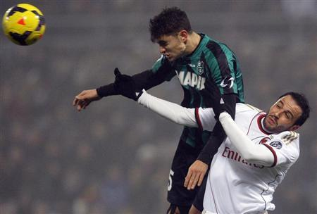 AC Milan's Pazzini jumps for the ball with Sassuolo's Antei during their Italian Serie A soccer match in Reggio Emilia