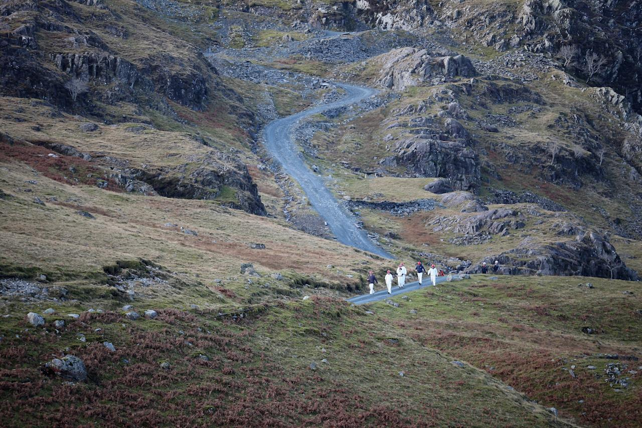 KESWICK, ENGLAND - DECEMBER 05:  Caldbeck cricket team walk from Honister Slate Mine, to go for tea,  after winning the world's first underground cricket match on December 5, 2013 in Keswick, England. The Christmas fixture between Caldbeck and Threlkeld took part 600m (2,000ft) inside Fleetwith Pike at  Englands last working slate mine at Honister in the Lake District. The game is one of many unusual venues the teams have played in to raise money to fix Threlkeld Cricket Club's flood damaged ground. The match was won by Caldbeck Village.  (Photo by Christopher Furlong/Getty Images)