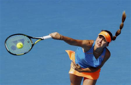 Belinda Bencic of Switzerland serves to Li Na of China during their women's singles match at the Australian Open 2014 tennis tournament in Melbourne