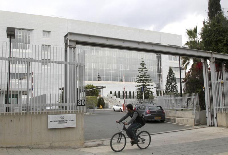 Man cycles pass the Central Bank of Cyprus on the island's capital Nicosia