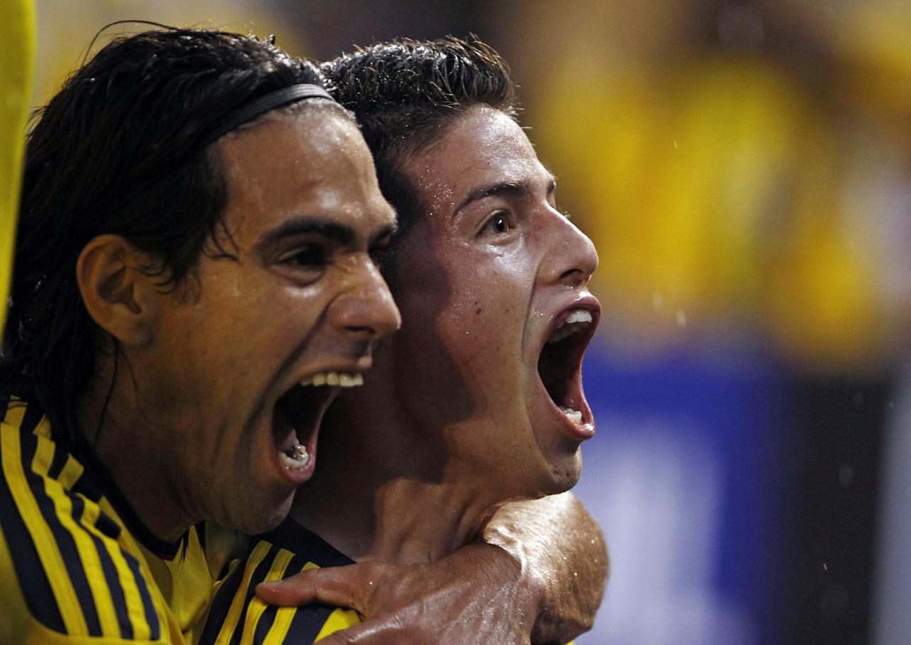 """FILE- In this Sept. 6, 2013, file photo, Colombia's James Rodriguez, right, celebrates with Radamel Falcao Garcia after scoring at a 2014 World Cup qualifying soccer match against Ecuador in Barranquilla, Colombia. The """"Coffee Growers"""" ripped through qualification, hammering Uruguay 4-0 on their way to earning 30 points from 16 matches. Falcao sealed qualification with two late goals against Chile, coming from behind for a 3-3 home draw. (AP Photo/Fernando Vergara, File)"""