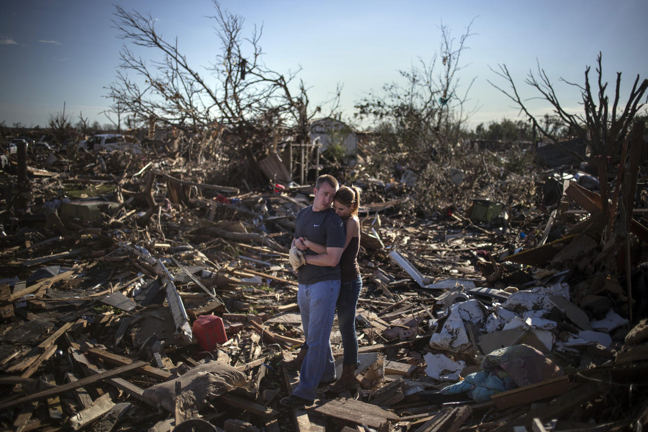 Danielle Stephan holds boyfriend Thomas Layton as they pause between salvaging through the remains of a family member's home one day after a tornado devastated the town Moore, Oklahoma, in the outskirts of Oklahoma City May 21, 2013. Rescuers went building to building in search of victims and thousands of survivors were homeless on Tuesday after a massive tornado tore through the Oklahoma City suburb of Moore, wiping out whole blocks of homes and killing at least 24 people.  REUTERS/Adrees Latif   (UNITED STATES - Tags: DISASTER ENVIRONMENT TPX IMAGES OF THE DAY) - RTXZVON