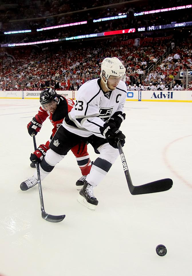 NEWARK, NJ - MAY 30:Dustin Brown #23 of the Los Angeles Kings handles the puck against Dainius Zubrus #8 of the New Jersey Devils  during Game One of the 2012 NHL Stanley Cup Final at the Prudential Center on May 30, 2012 in Newark, New Jersey.  (Photo by Elsa/Getty Images)