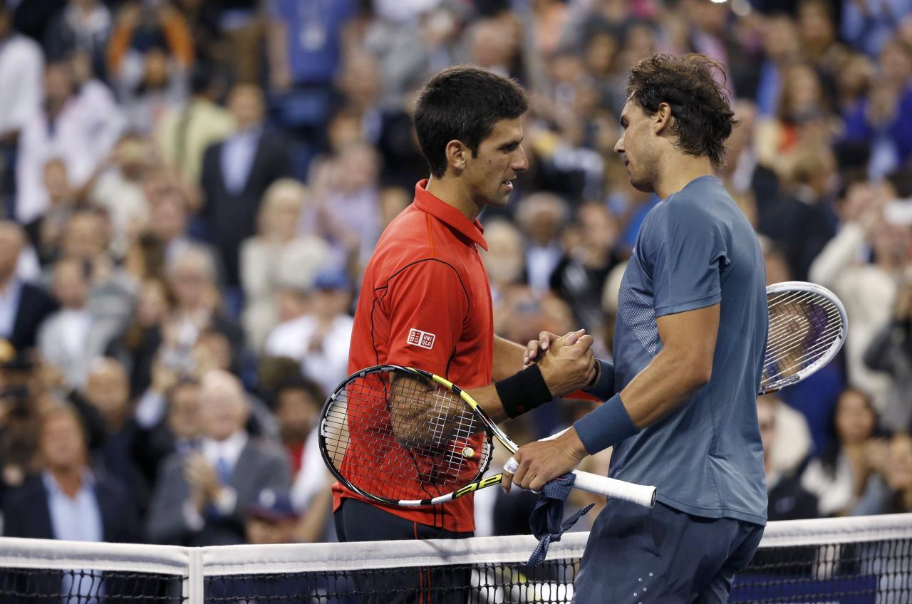 Rafael Nadal of Spain is congratulated by Novak Djokovic of Serbia (L) after his victory in their men's final match at the U.S. Open tennis championships in New York, September 9, 2013. REUTERS/Mike Segar (UNITED STATES - Tags: SPORT TENNIS)
