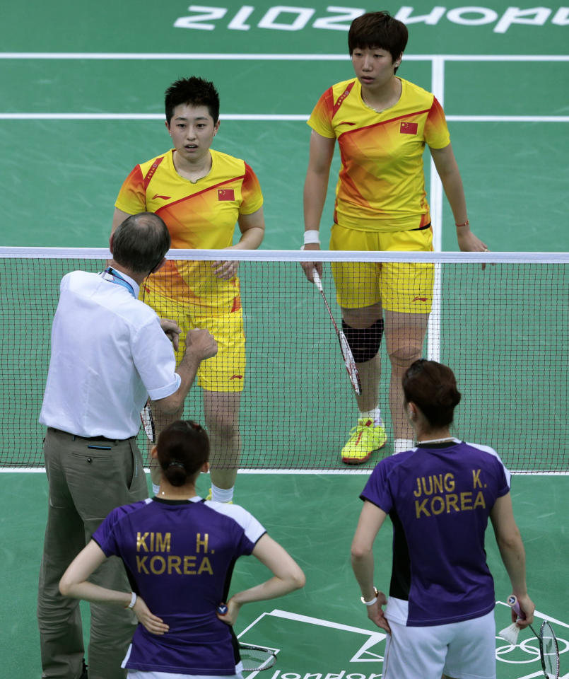 An unidentified official talks to world doubles champions Yu Yang, left, and Wang Xiaoli, as South Korea's Jung Kyung-eun, right, and Kim Ha-na, listen during their women's doubles badminton match at the 2012 Summer Olympics, Tuesday, July 31, 2012, in London. Wang and Yu and their South Korean opponents were booed loudly at the Olympics on Tuesday for appearing to try and lose their group match in Wembley Arena to earn an easier draw. (AP Photo/Saurabh Das)