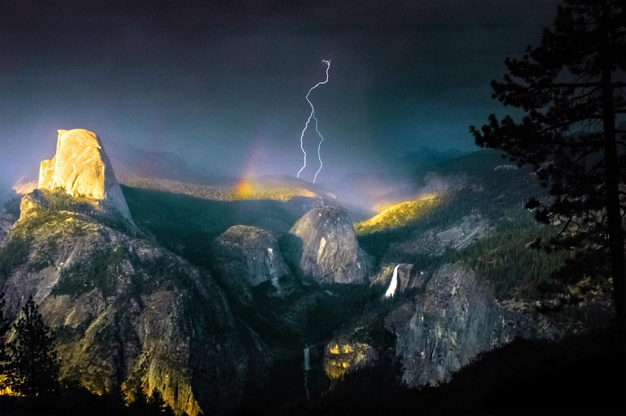 PIC BY NOLAN NITSCHKE / CATERS NEWS - (PICTURED A rainbow and lightning bolt is visible) This is the spectacular moment a photographer struck gold - by capturing a bolt of lightning cracking through a rainbow in a freak weather display. The extraordinary one-of-a-kind sighting was captured by keen photographer Nolan Nitschke, 27, while on a trip to Yosemite National Park in California, USA. Nolan knew a storm was approaching the area and that the incredible rocky peaks throughout the park act as lightning rods but had no idea he would capture such a breathtaking moment. After spending hours painstakingly trying for the perfect shot he finally hit the jackpot as the bright lightning crashed through the colourful rainbow lighting up the dark sky. SEE CATERS COPY