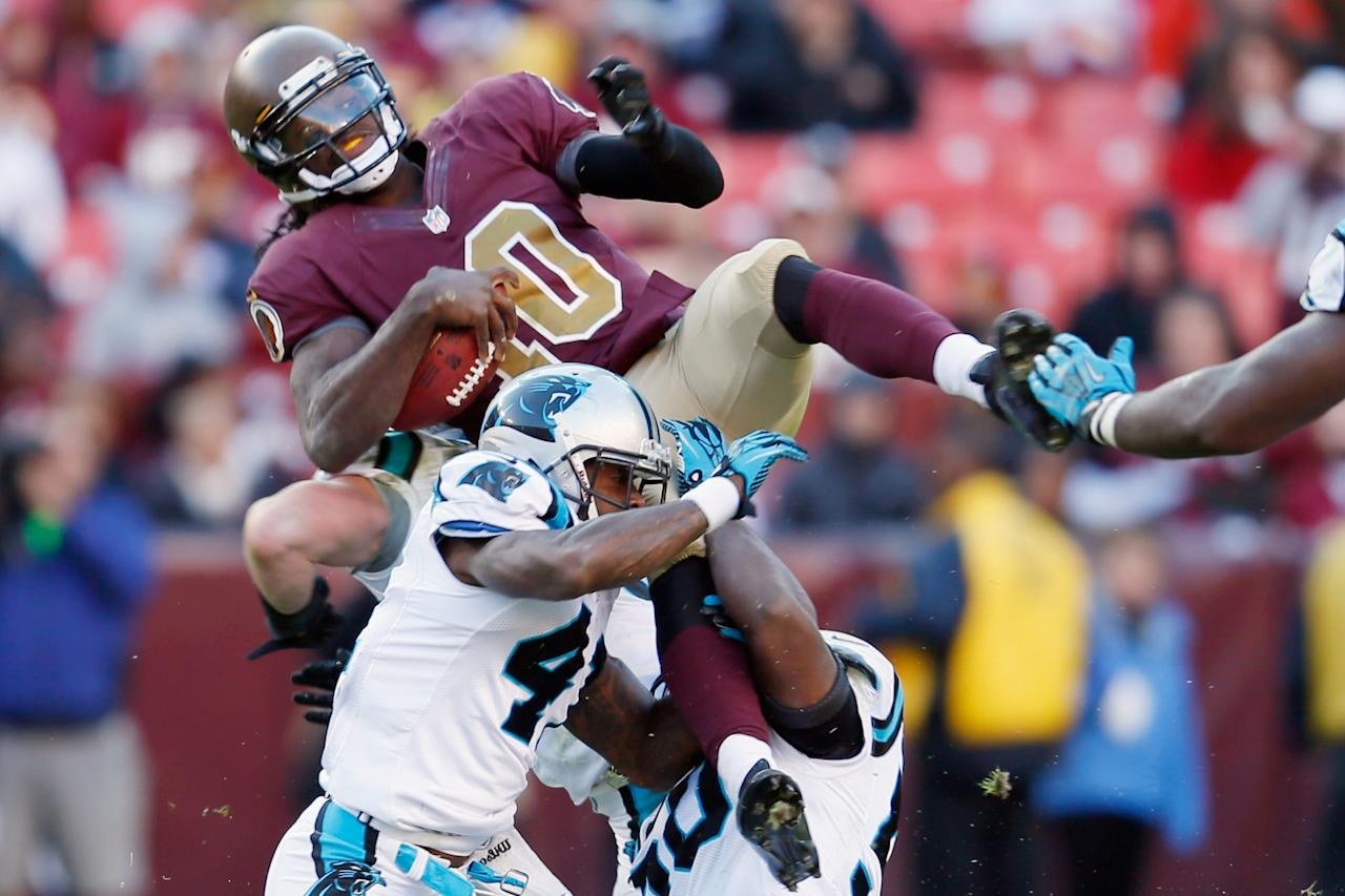LANDOVER, MD - NOVEMBER 04: Quarterback Robert Griffin III #10 of the Washington Redskins is tackled by Captain Munnerlyn #41 and James Anderson #50 of the Carolina Panthers during the fourth quarter of the Panthers 21-13 win at FedExField on November 4, 2012 in Landover, Maryland.  (Photo by Rob Carr/Getty Images)