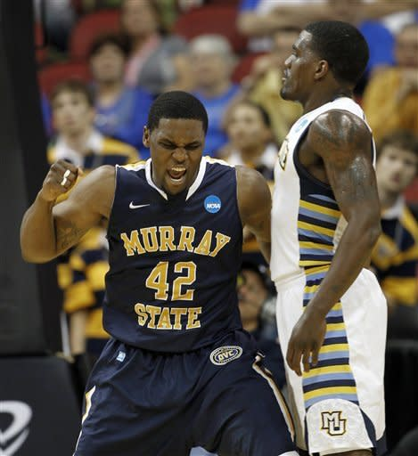 Murray State forward Ivan Aska (42) reacts as Marquette guard Darius Johnson-Odom looks on in the first half of their NCAA third-round tournament college basketball game in Louisville, Ky., Saturday, March 17, 2012. (AP Photo/John Bazemore)