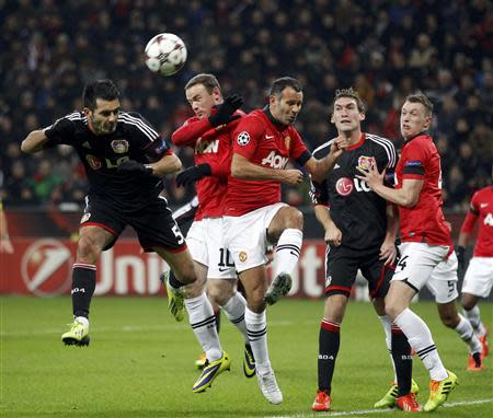 Bayer Leverkusen's Spahic is challenged by Manchester United's Rooney and Giggs during Champions League soccer match in Leverkusen