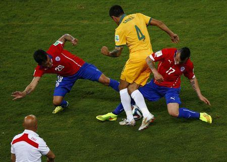 Chile's Aranguiz and Chile's Medel fights for the ball with Australia's Cahill uring their 2014 World Cup Group B soccer match at the Pantanal arena in Cuiaba