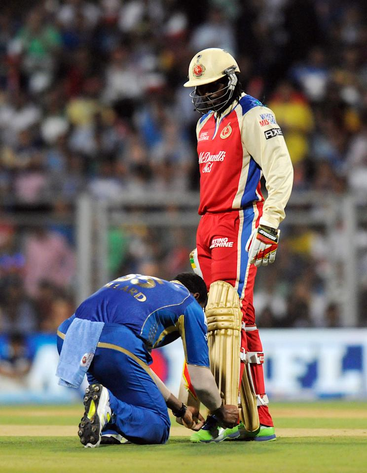Kieron Pollard of Mumbai Indians helps Chris Gayle of Royal Challengers Bangalore during match 37 of the Pepsi Indian Premier League ( IPL) 2013  between The Mumbai Indians and the Royal Challengers Bangalore held at the Wankhede Stadium in Mumbai on the 27th April 2013. (BCCI)