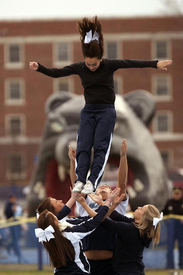 Maine cheerleaders practice routines before the start of an NCAA football game against Rhode Island in Orono, Maine, Saturday, Nov. 16, 2013. (AP Photo/Michael C. York)