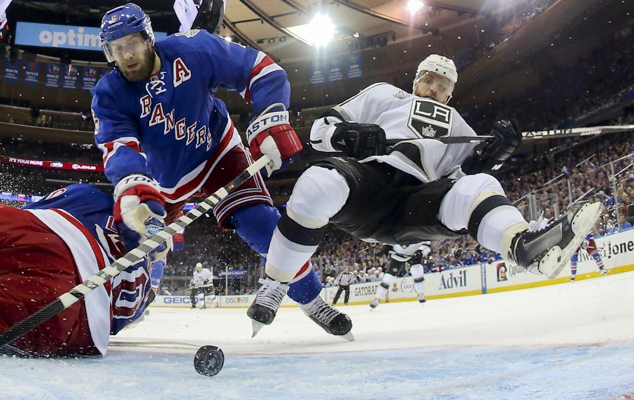 Los Angeles Kings right wing Marian Gaborik (12), right, falls as New York Rangers defenseman Dan Girardi (5) looks to clear the puck away from the goal in the third period during Game 3 of the NHL hockey Stanley Cup Final, Monday, June 9, 2014, in New York. (AP Photo/Bruce Bennett, Pool)