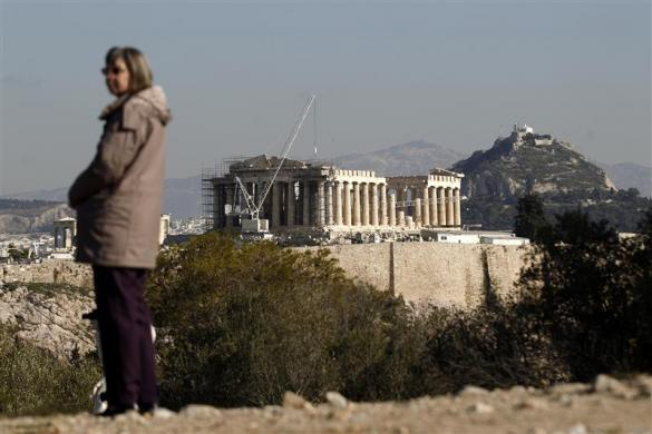 A woman stands at the Filopappou hill opposite the Parthenon temple in Athens January 19, 2012.