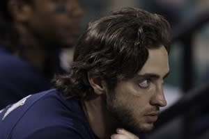 Milwaukee Brewers' Ryan Braun and Rickie Weeks watch from the dugout during the ninth inning of Game 5 of baseball's National League championship series against the St. Louis Cardinals Friday, Oct. 14, 2011, in St. Louis. The Cardinals won 7-1 to take a 3-2 lead in the series. (AP Photo/Matt Slocum)