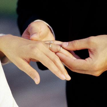 Close-up-of-a-groom-placing-a-ring-on-his-brides-finger_web