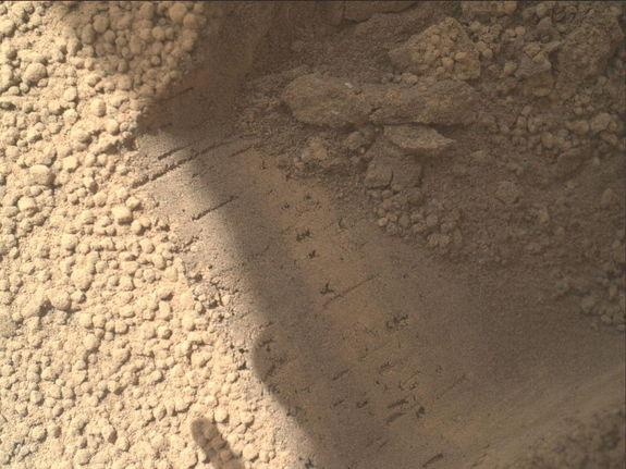 This image contributed to an interpretation by NASA's Mars rover Curiosity science team that some of the bright particles on the ground near the rover are native Martian material. Other light-toned material nearby has been assessed as small deb