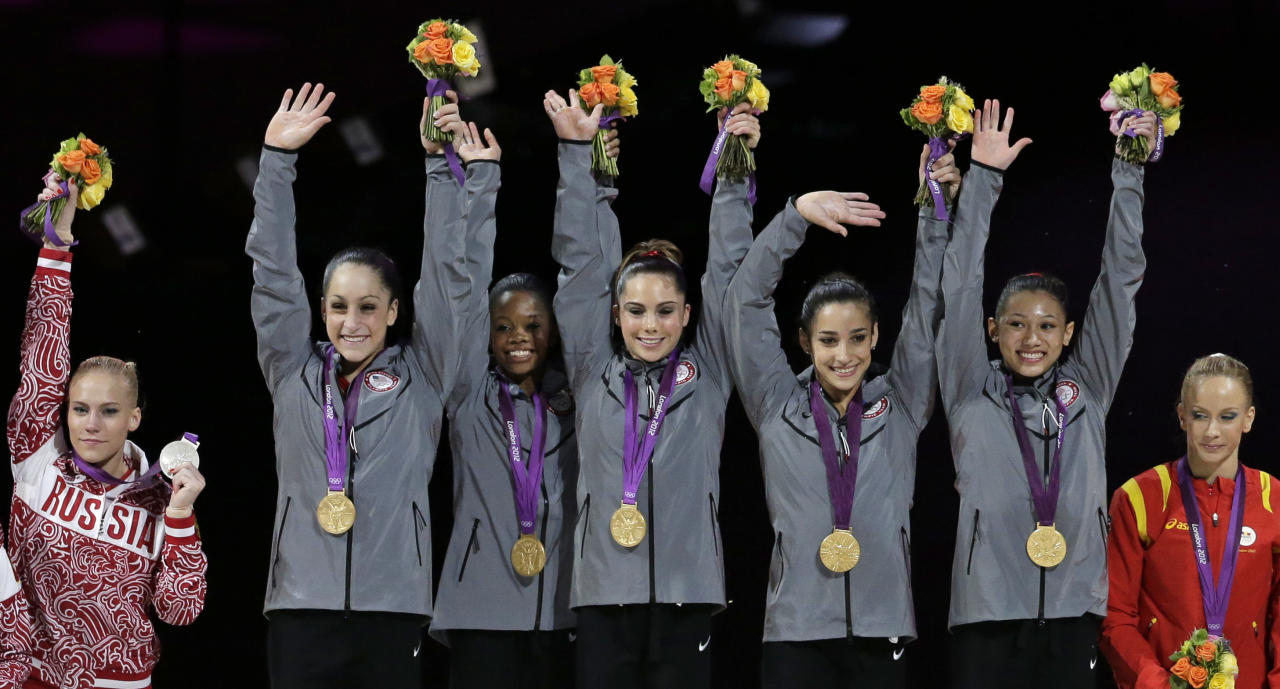 U.S. gymnasts, top left to right, Jordyn Wieber, Gabrielle Douglas, McKayla Maroney, Alexandra Raisman, Kyla Ross raise their hands on the podium, next to Romania's Sandra Raluca Izbasa, right, and Russian gymnast Kseniia Afanaseva, left, during the medal ceremony during the Artistic Gymnastic women's team final at the 2012 Summer Olympics, Tuesday, July 31, 2012, in London.  Team U.S. won the gold. (AP Photo/Gregory Bull)