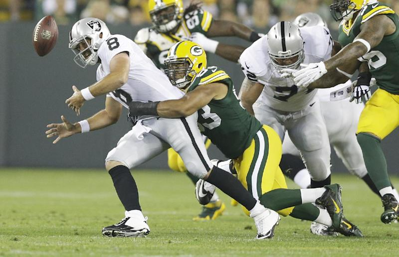 Oakland Raiders quarterback Matt Schaub (8) fumbles as he is hit by Green Bay Packers' Nick Perry during the first half of an NFL preseason football game Friday, Aug. 22, 2014, in Green Bay, Wis. The Packers recovered the fumble