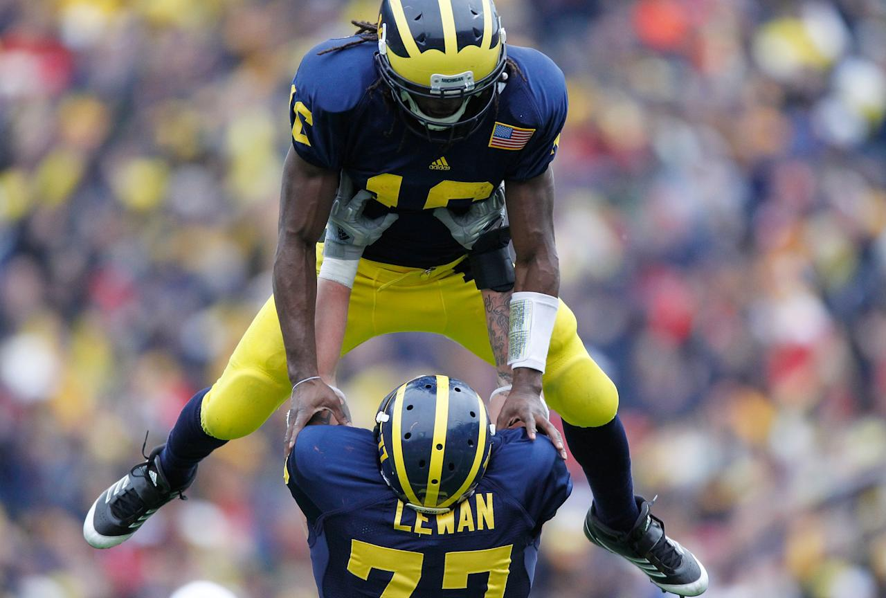 ANN ARBOR, MI - NOVEMBER 19: Denard Robinson #16 of the Michigan Wolverines celebrates a fourth quarter touchdown with Taylor Lewan #77 while playing the Nebraska Cornhuskers at Michigan Stadium on November 19, 2011 in Ann Arbor, Michigan. Michigan won the game 45-17. (Photo by Gregory Shamus/Getty Images)