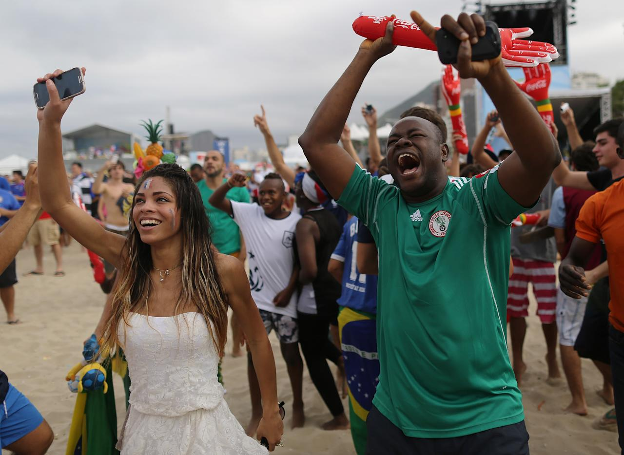 Nigeria and France soccer fans dance before their team's World Cup round of 16 match previous a live telecast inside the FIFA Fan Fest area on Copacabana beach in Rio de Janeiro, Brazil, Monday, June 30, 2014. (AP Photo/Leo Correa)