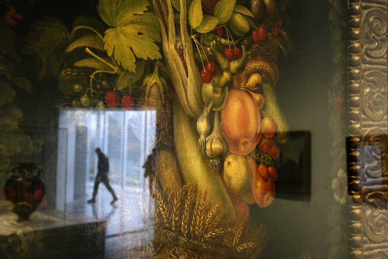 "A silhouetted man is reflected in the glass of ""L'Ete"", a painting by Arcimboldo Giuseppe in the Louvre Museum in Lens."