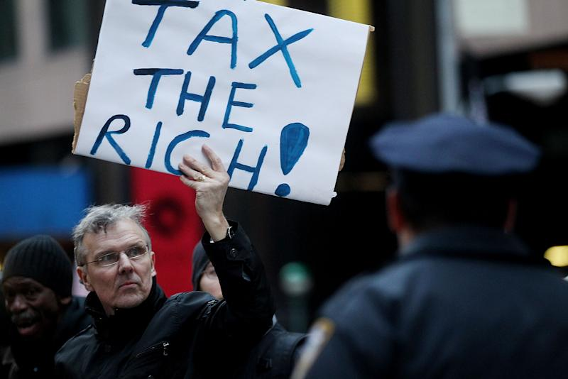 "NEW YORK, NY - MARCH 24:  A protester holds a ""Tax the Rich"" sign as he marches during a rally against budget slashing held by union supporters on March 24, 2011 in New York City. The protesters called for closing tax loopholes for the wealthy and ending budget cuts for social programs. (Photo by Mario Tama/Getty Images)"