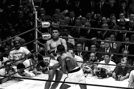 Cassius Clay and Sonny Liston face off in a WBA/WBC World Heavyweight fight in this Miami Herald archive photo