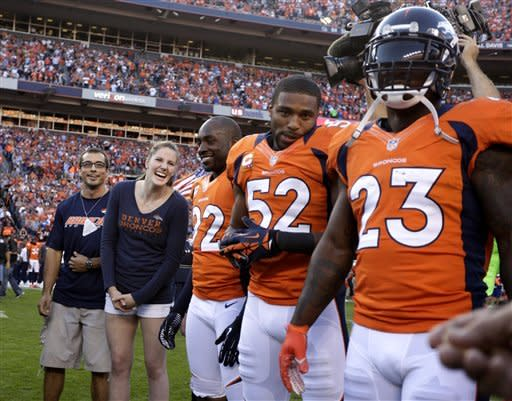 Olympic gold medalist Missy Franklin, second from left, laughs while in the coin toss huddle with the Denver Broncos and the Pittsburgh Steelers  players before their NFL football game, Sunday, Sept. 9, 2012, in Denver. (AP Photo/Joe Mahoney)