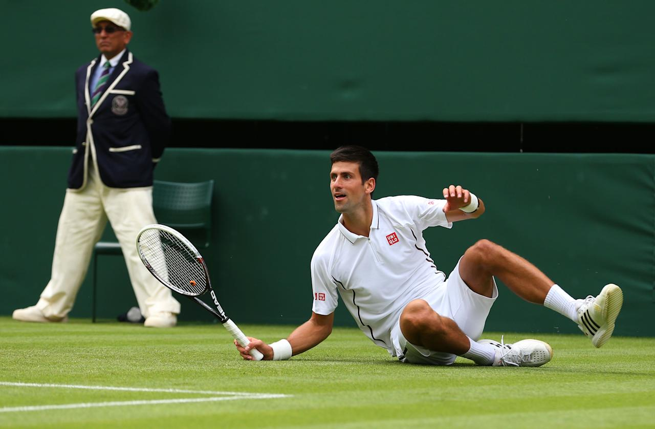LONDON, ENGLAND - JUNE 25: Novak Djokovic of Serbia slips during his Gentlemen's Singles first round match against Florian Mayer of Germany on day two of the Wimbledon Lawn Tennis Championships at the All England Lawn Tennis and Croquet Club on June 25, 2013 in London, England. (Photo by Julian Finney/Getty Images)