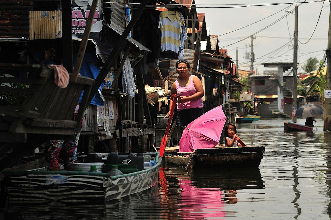 MANILA, PHILIPPINES - APRIL 28:  Residents uses makeshift boats to get around in Artex Compound in Malabon City on April 28, 2013 in Manila, Philippines. The residents of the former textile compound had to adjust their daily lives after  flood waters submerged their low-lying village in 2004.  (Photo by Veejay Villafranca/Getty Images)