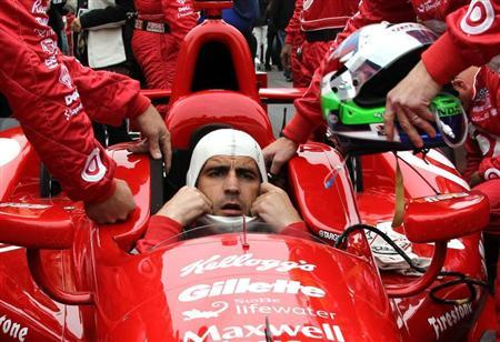 Driver Dario Franchitti of Britain dons his headgear ahead of the 97th running of the Indianapolis 500 at the Indianapolis Motor Speedway in Indianapolis
