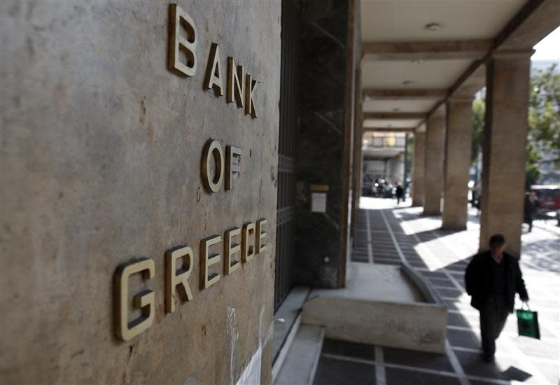 A man walks outside the Bank of Greece headquarters in Athens