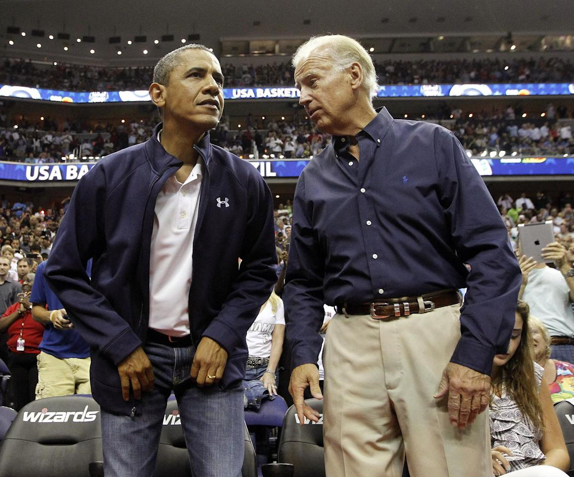 President Barack Obama, left, and Vice President Joe Biden take their seats as they attend an Olympic men's basketball exhibition game between Brazil and Team USA in Washington, Monday, July 16, 2012. (AP Photo/Pablo Martinez Monsivais)